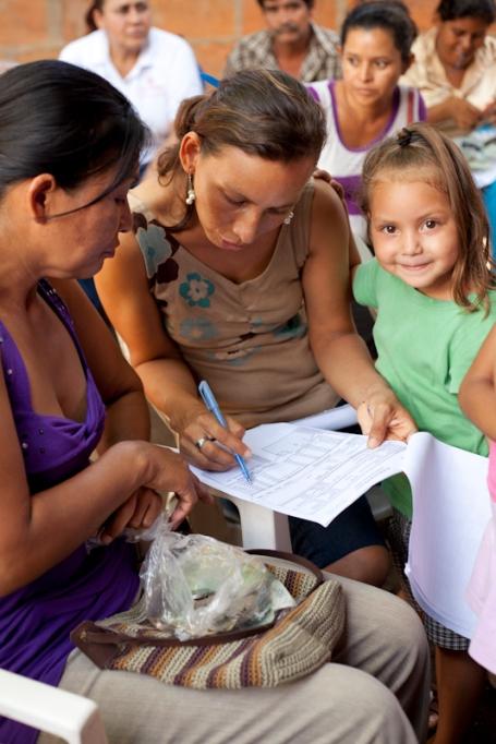 La hija de una clienta de Pro Mujer participa de una reunión de banco comunal con su madre